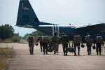 Soldiers walking towards a military plane