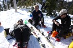 Young people taking a break with their skis in the snow
