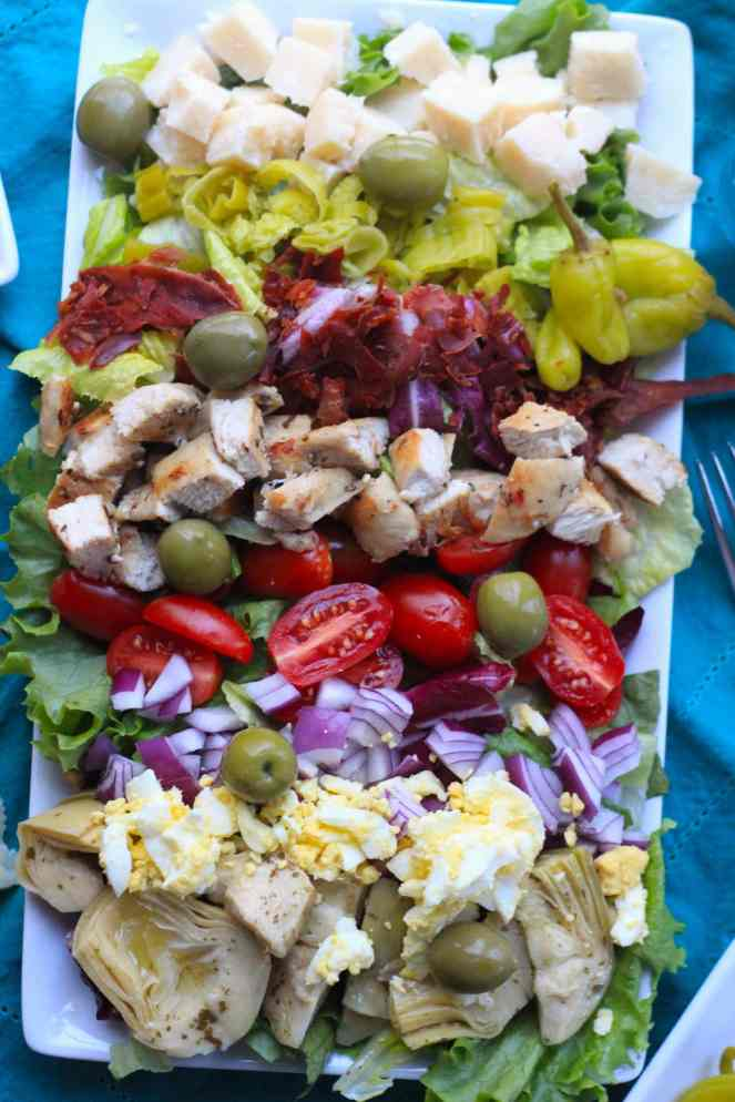 This Italian Cobb Salad packs a serious flavor punch! There are a few traditional Cobb ingredients in this recipe (such as hard boiled eggs and tomatoes). But every other ingredient gets an Italian twist: the chicken is marinated in an herby red wine vinaigrette. The bacon is made from prosciutto. The cheese is a crunchy Grana Padano. Marinated artichokes, olives, and pickled peppers also transform this classic in to an updated, healthy, and impressive salad! | #SoHappyYouLikedIt