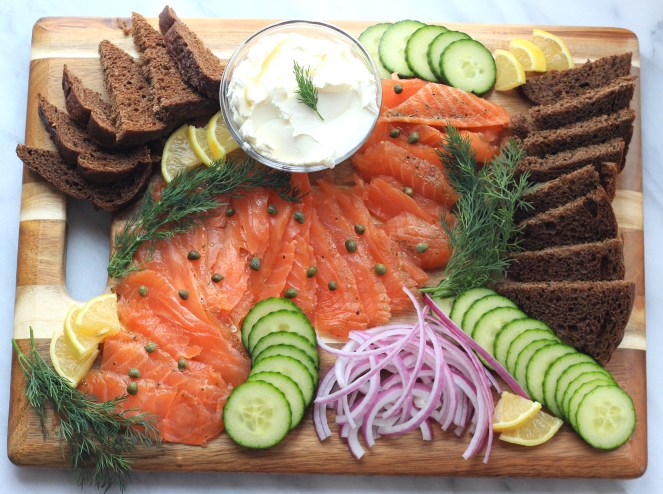 Lox is a traditional and well-loved holiday appetizer! Salmon is cured with smoked sea salt, brown sugar, and pepper. Served alongside a creamy goat cheese schmear, fresh cucumbers, red onion, salty capers, soft pumpernickel, dill, and lemon - this is an appetizer spread that is sure to please! | #SoHappyYouLikedIt