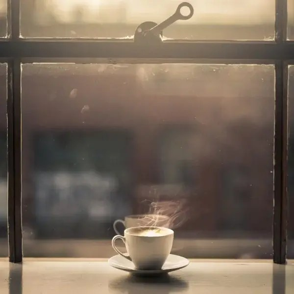 Warm cup of coffee infront of a window