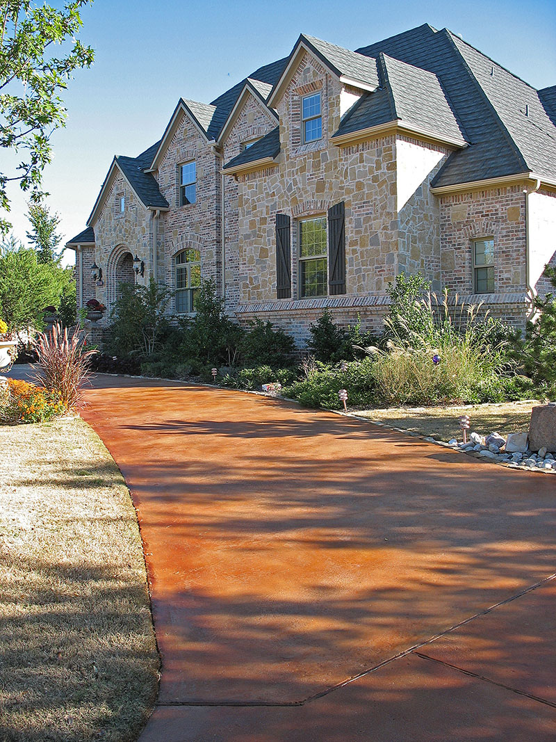 acid stained concrete driveway with house