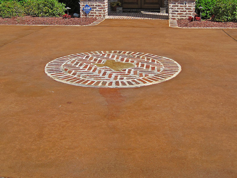 brick ring in the center of an acid stained driveway