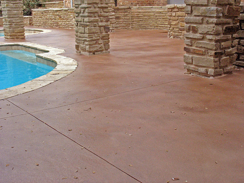 closer view of stone columns on pool deck that had a brown skim coat overlay