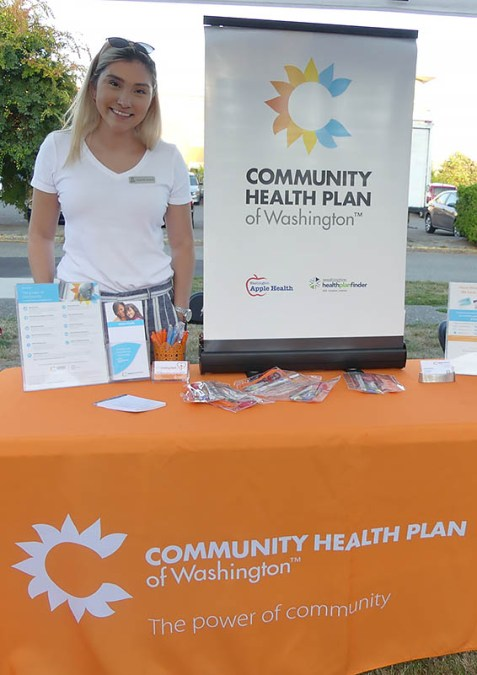 Woman stands at Community Health Plan of Washington table & display.
