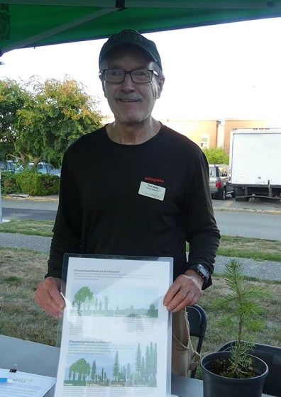 Man holds up a graphic of trees at the Green Seattle table.