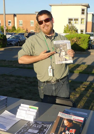 Magnuson Community Center's Doug Oaksford holds up some print materials.