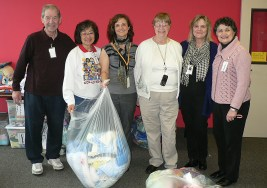 Harry & other KIA (Knit It Alls) volunteers bag up warm knitted items for donation, Nov. 2012