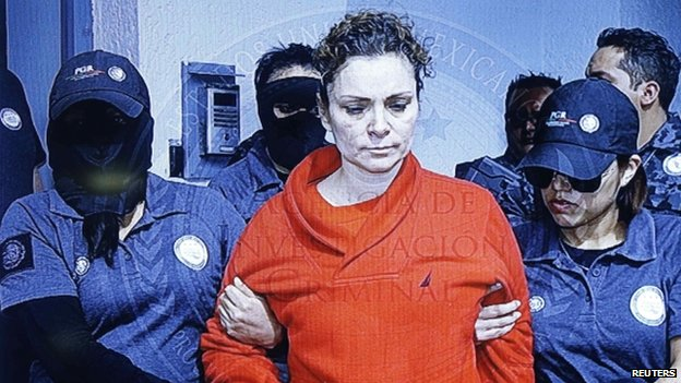 Maria de los Angeles Pineda Villa, the wife of the former mayor of Iguala, Jose Luis Abarca, as seen displayed on a television screen during a news conference, while she is transferred to a high security jail.