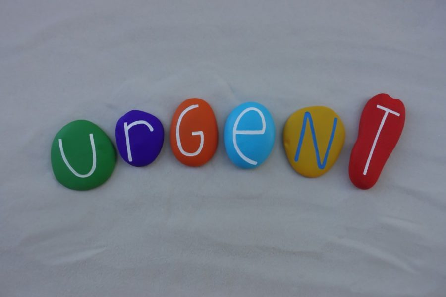 urgent-word-composed-with-multi-colored-stones-over-white-sand_t20_B87wQY (1)