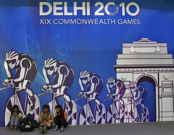 An official billboard for Delhi 2010 with dark blue background shows a team of cyclists riding through an arc