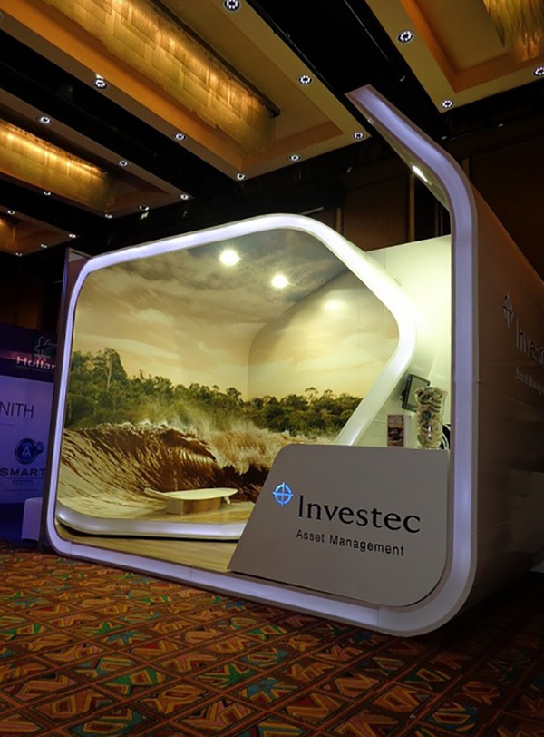 Investec exhibition stand swirls round and has an image throughout it that looks like an ocean and you sit on a surfboard