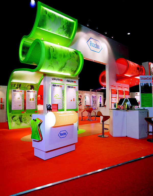 Quirky Roche exhibition stand has red carpeting, red high chairs and a green banner