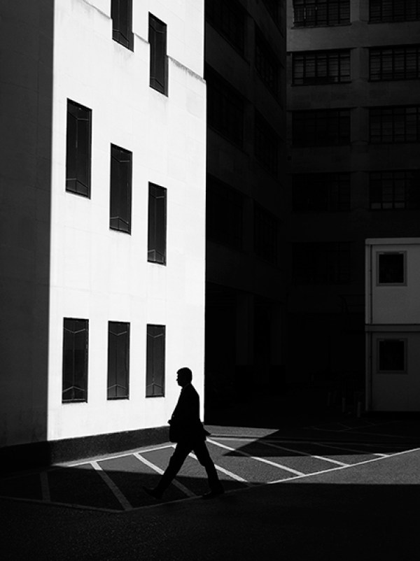 Black and white, light and shadow effect photograph with a bright-white building with blackened out windows and a black, silhouette of a man walking past