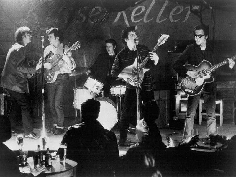 Paul McCartney (Gary Bakewell), George Harrison (Chris O'Neill), Pete Best (Scot Williams), John Lennon (Ian Hart), and Stuart Sutcliffe (Stephen Dorff) perform as The Beatles at the Kaiserkeller in Backbeat.