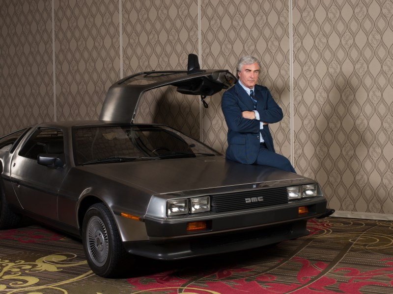 Alec Baldwin posing with Production DMC leaning on fender in Framing John DeLorean.