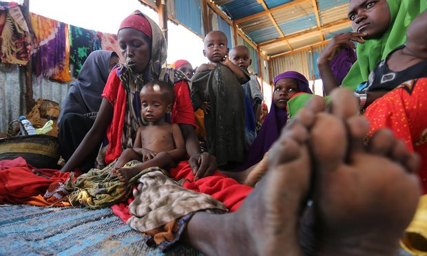 A Somali woman sits with her children inside the shelter at the Al-cadaala camp in Mogadishu. Three consecutive years of drought have brought Somalia to the brink of famine. Photograph: Feisal Omar/Reuters