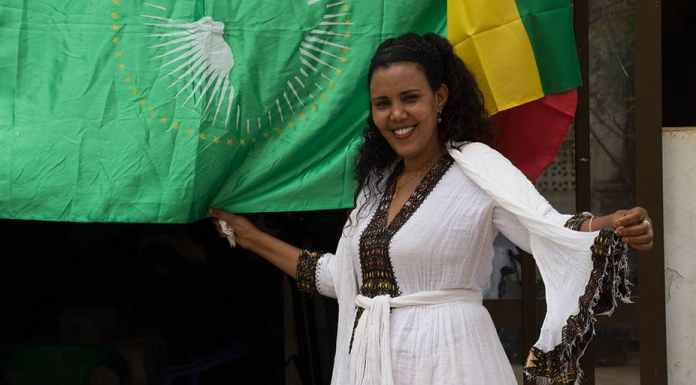 A woman holds the flags of the African Union and Ethiopia during celebrations to mark the Ethiopian New Year Sabir Olad/Wikimedia Commons