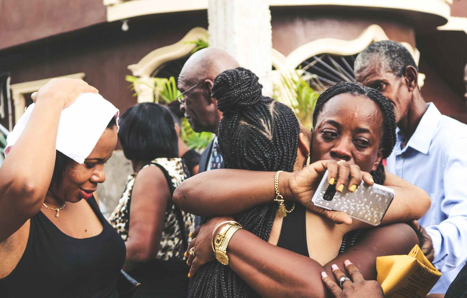 upset black woman embracing anonymous girlfriend near group of people