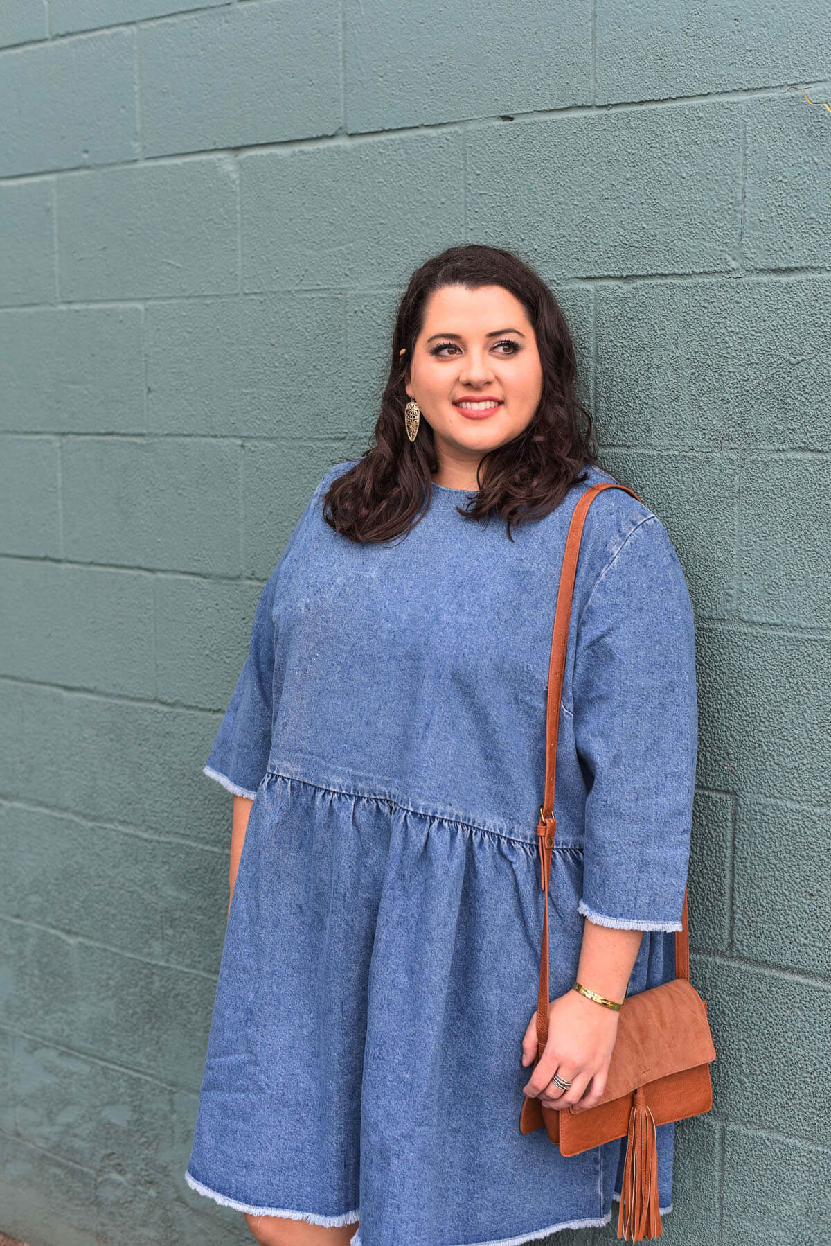 Spring style in a denim dress. Emily Bastedo, curvy style blogger from Something Gold, Something Blue features this comfortable and versatile dress perfect for running errands or a night on the town. She's currently ready to go to brunch with a statement heel, small clutch and bold earrings. Brunch style, spring style, plus size style, plus size fashion, floral