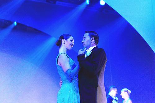 A pair of ballroom dancers pose.