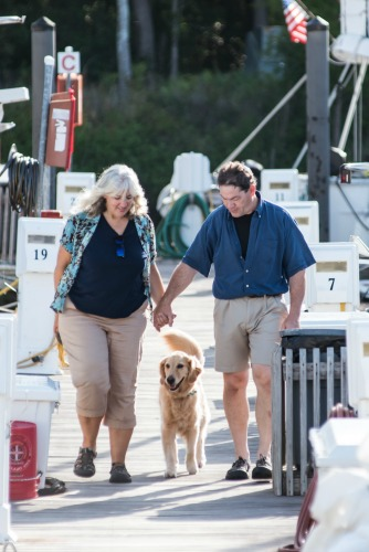 Pam and Mike holding hands with Honey the golden retriever.
