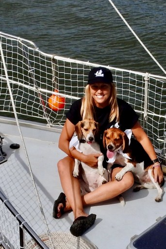 Avoid disaster with dogs in rough seas (woman in ball cap with two beagles on bow of a sailboat)