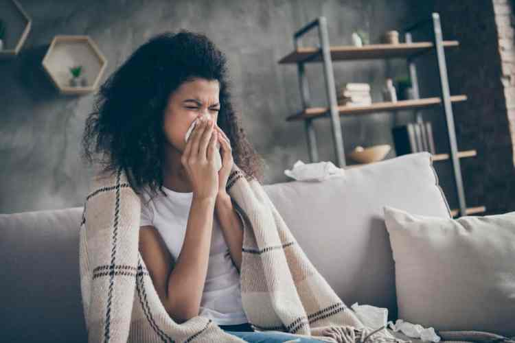 A sick woman at home with a blanket