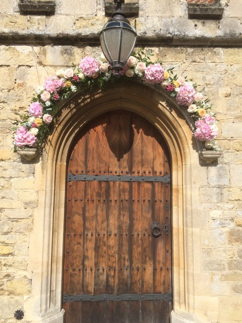 Pastel pink and peach flower arch at Notley Abbey