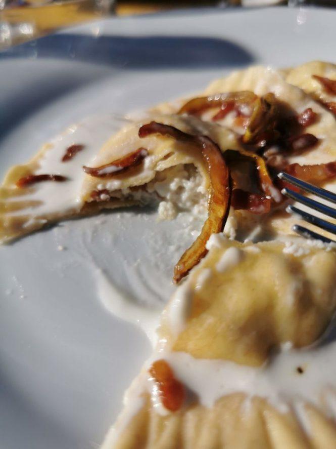 Cappellacci pere caramellate e pancetta croccante su fonduta di pecorino