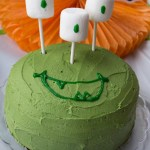 Green monster birthday cake with marshmallow eyes on a decorated table (with simple title overlay)