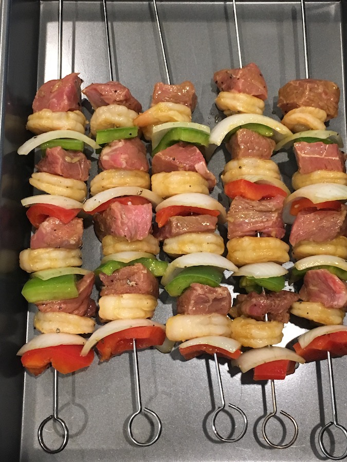 Prepared steak and shrimp kabobs on metal skewers in a metal pan