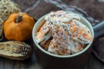 Halloween candy bark pieces in a brown bowl next to fall decorations on a wooden surface