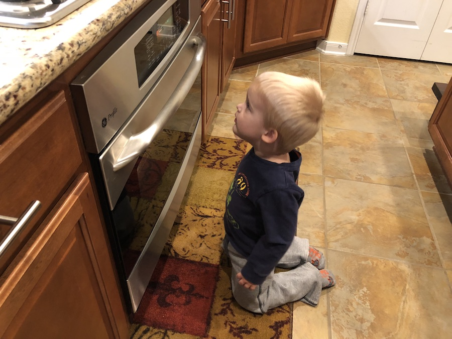 Young boy kneeling in front of an oven waiting for cookies to bake
