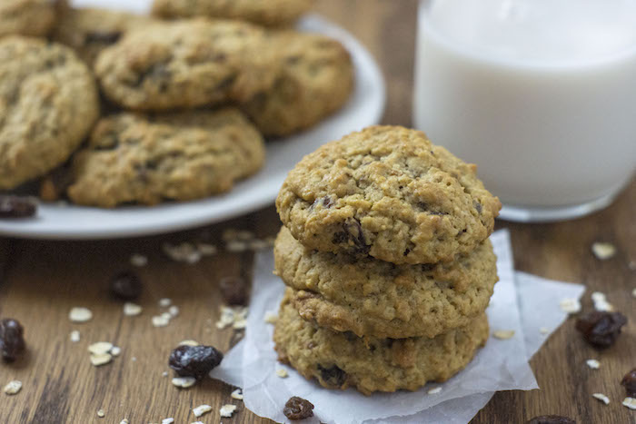 Three oatmeal raisin cookies stacked on pieces of parchment paper with oats and raisins around them with a plate of cookies and a glass of milk behind all on a wooden surface