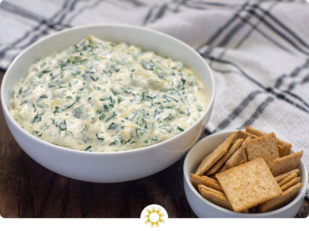 Round white bowl full of spinach artichoke dip with a small round white bowl of crackers in front and a white and grey towel behind all on a wooden surface (with logo overlay)