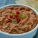 Chili nacho dip in a white bowl with chips in the background on a bamboo board
