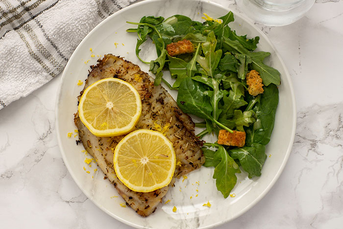 Top-down view of Lemon Rosemary Tilapia on a marbled plate with salad beside it on a grey marbled surface with a towel and glass of water