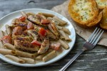 Cajun Chicken Pasta on a white plate with a fork to the right side and garlic toast in the background on a wooden surface