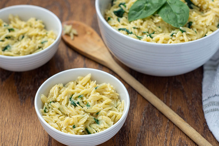 Cheesy Spinach Orzo Pasta Sides in a small white bowl next to a wooden spoon with two more bowls in the background all on a wooden surface