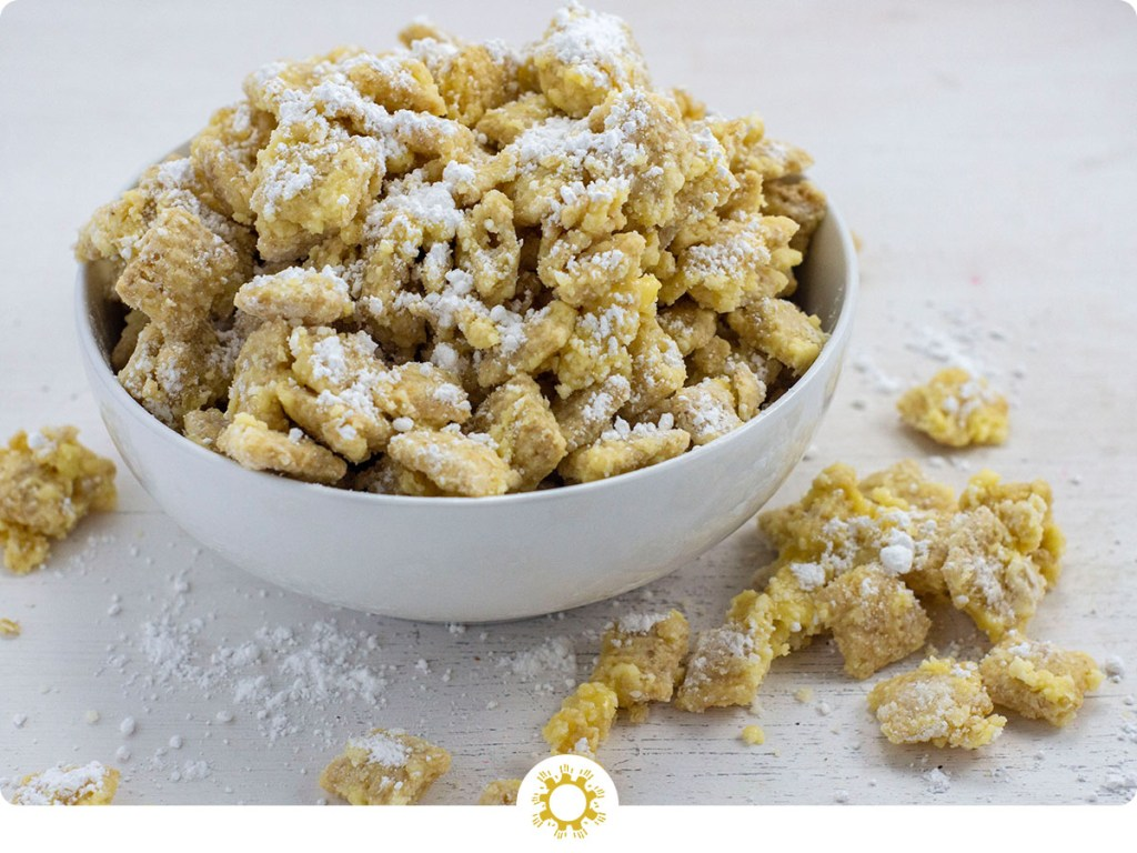 Banana cream puppy chow sprinkled with powdered sugar in a round white bowl with pieces around the bowl on a white surface (with logo overlay)