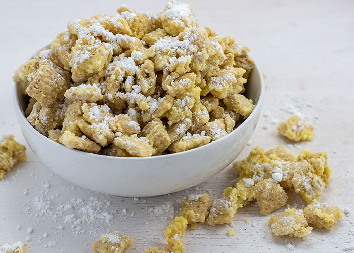 Banana cream puppy chow sprinkled with powdered sugar in a round white bowl with pieces around the bowl on a white surface
