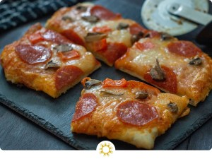 Pieces of pizza topped with sauce, cheese, pepperoni, and mushrooms on a slate serving plate next to a pizza cutter on a wooden surface (with logo overlay)