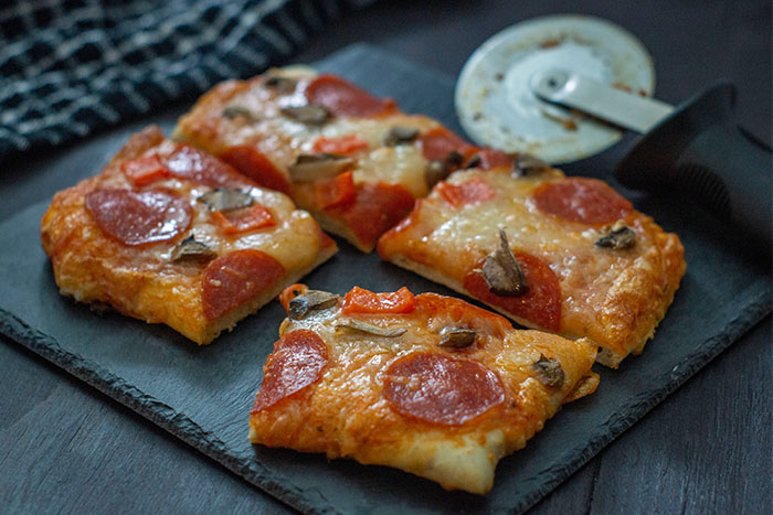 Pieces of pizza topped with sauce, cheese, pepperoni, and mushrooms on a slate serving plate next to a pizza cutter on a wooden surface
