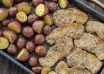 Cooked potatoes and ranch pork on a metal sheet pan next to a wooden spoon on a wooden surface