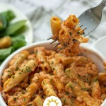 Baked ziti in a white bowl (vertical with title overlay)