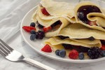 Multiple breakfast crepes filled with chocolate sauce and berries and garnished with powdered sugar on a white plate with a white napkin behind and a fork near the front on a grey marbled surface