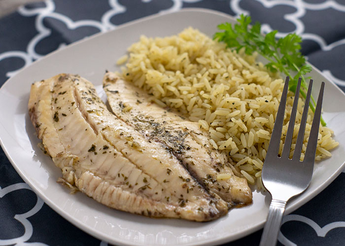Cilantro and lime juice covered fish fillets next to cilantro lime rice with a sprig of fresh cilantro on a square white plate with a stainless steel fork on a white and grey placemat on a wooden surface