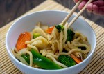 Round white bowl of vegetable lo mein with a pair of chopsticks pulling out some noodles, onion, and broccoli on top of a bamboo placement on a wooden surface