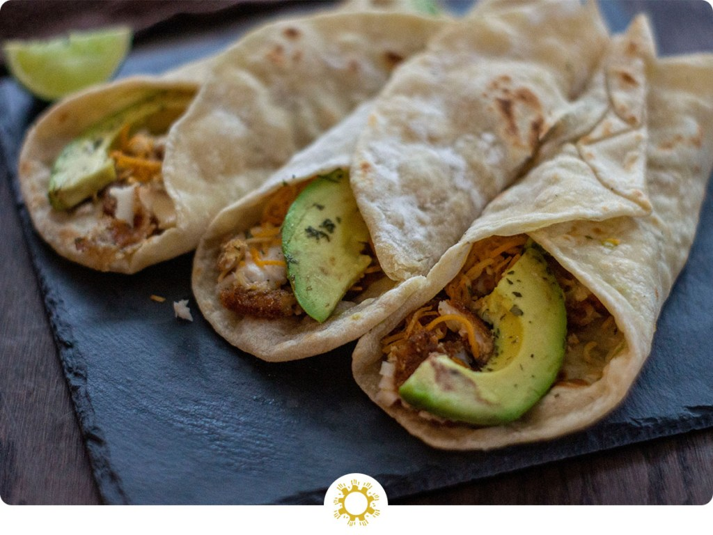 Avocado fish tacos rolled up and ready to eat with logo overlay